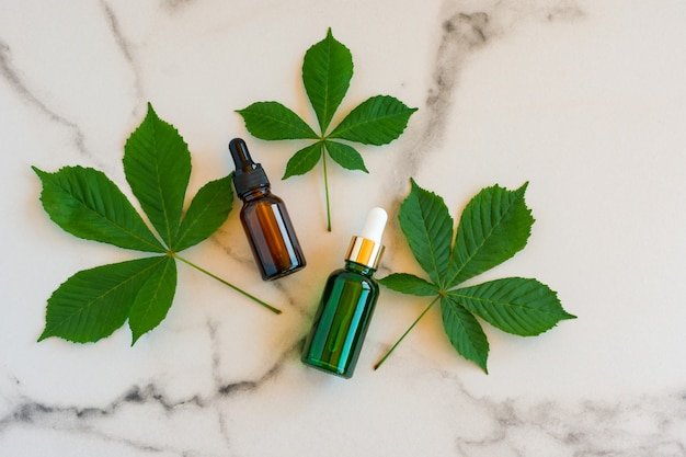 Serum do twarzy w szklanych buteleczkach z pipetą, zielone liście na marmurowym tle. pusty pakiet etykiet na makiety brandingowe. koncepcja kosmetyków wiosna. naturalny organiczny produkt kosmetyczny.