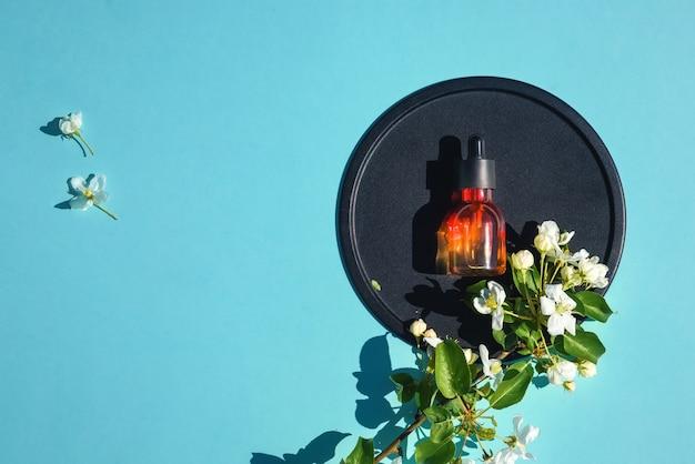 Serum, eliksir, perfumy do urody płasko leżały na niebieskim stole. pojęcie naturalnych organicznych kosmetyków i perfum. minimalizm