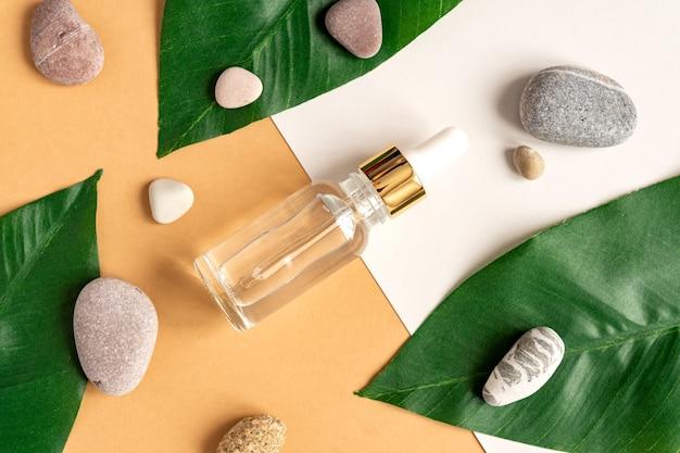 Serum kolagenowe do twarzy w przezroczystej szklanej butelce z zielonymi liśćmi