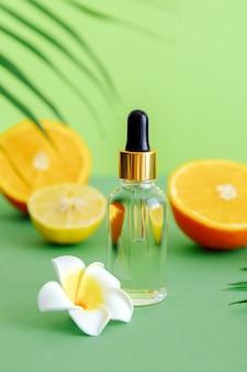 Serum kosmetyczne witamina c w szklanej butelce z pipetą z zakraplaczem cytrusów i kwiatem plumerii. pomarańczowy olejek eteryczny ze składnikami cytrusowymi witamina c kolor zielone tło. kosmetyki z naturalnym olejkiem spa.
