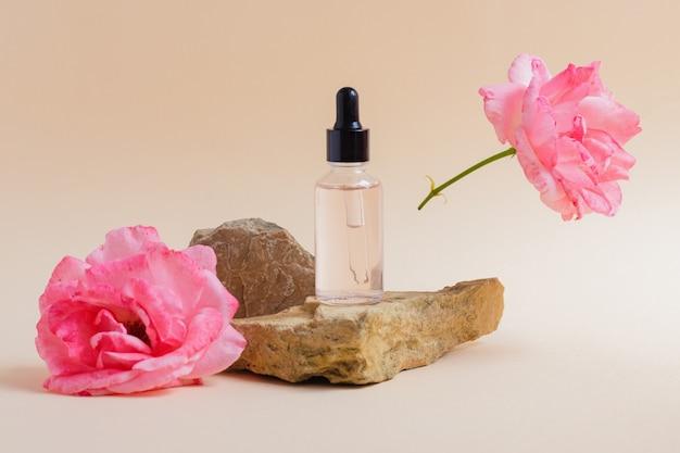 Serum lub płyn kosmetyczny, olejek na kamieniu obok kwiatu róży
