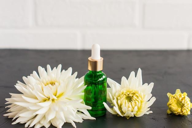 Serum nawilżające w butelce kosmetycznej z pipetą wykonaną z zielonego szkła na tle białej ceglanej ściany i kwiatów.