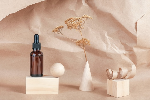 Serum, olejki eteryczne lub płynny kolagen w butelce z brązowego szkła z pipetką, drewnianymi geometrycznymi kształtami i suszonymi kwiatami na beżu