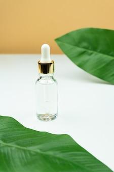 Serum przeciw starzeniu w szklanej butelce z zakraplaczem na zielonym liściu i białym tle. płynne serum do twarzy z kolagenem i peptydami. esencja pielęgnacyjna dla pięknej, zdrowej skóry.