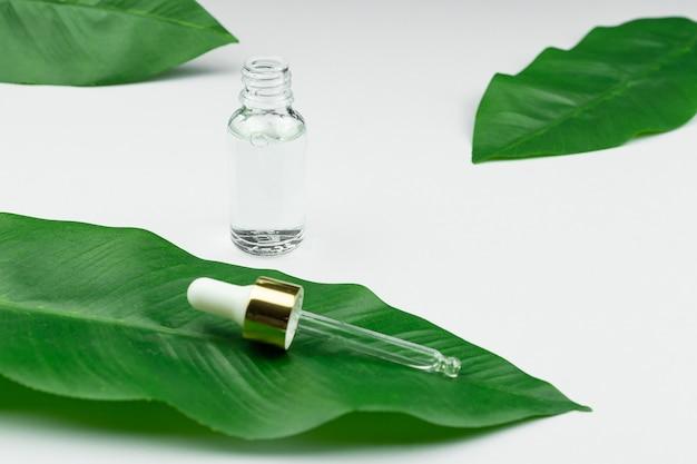 Serum przeciw starzeniu w szklanej butelce z zakraplaczem na zielonym liściu i białym tle.
