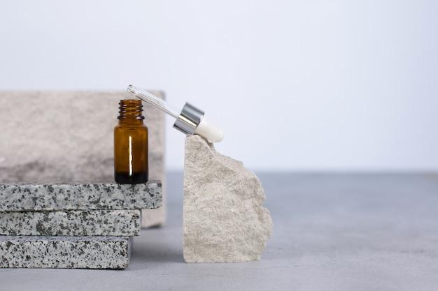 Serum w brązowych buteleczkach z zakraplaczem na naturalnym kamieniu