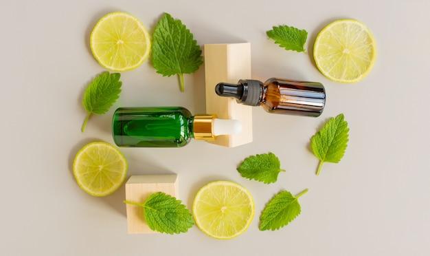 Serum z witaminą c. olejek cytrynowy. brązowo-zielona szklana butelka z pipetą, plasterki cytryny z listkami mięty na szarym tle. pojęcie zdrowia i urody. organiczne kosmetyki naturalne.