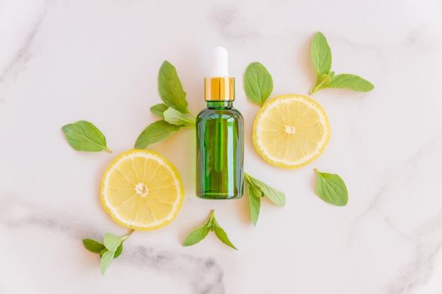 Serum z witaminą c w buteleczce kosmetycznej z plasterkami cytryny i cytrusów z zielonymi liśćmi na marmurowej powierzchni