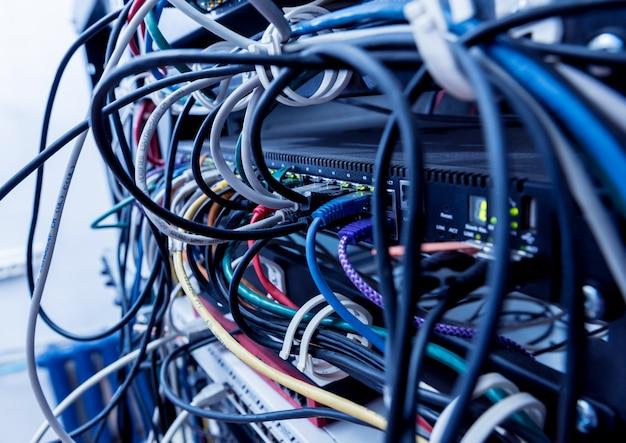 Serwerownia z komputerami do internetu. kable sieciowe podłączone do przełączników.