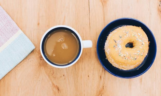 Serwetka; filiżanka kawy; pączek na drewniane tło