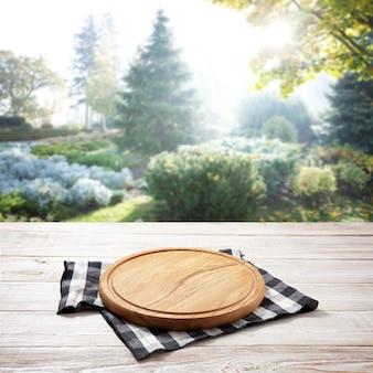 Serwetka i deska do pizzy na drewnianym biurku. letni krajobraz.