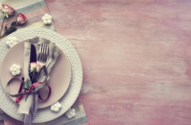 Serwetka i naczynia, ozdobione różanym pączkiem i wstążkami, wokół ceramiczne kwiaty i różowe róże