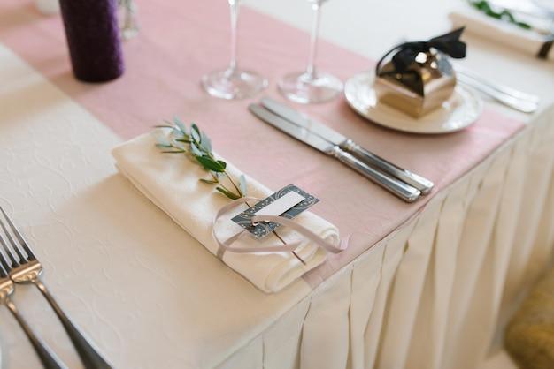 Serwetka ozdobiona kartą gościa i gałęzią eukaliptusa w porcji świątecznego stołu na weselu