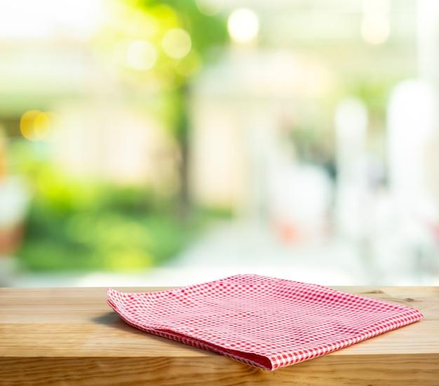 Serwetka z tkaniny na drewnianym stole z tłem szklanego okna. do wyeksponowania ekspozycji produktu.