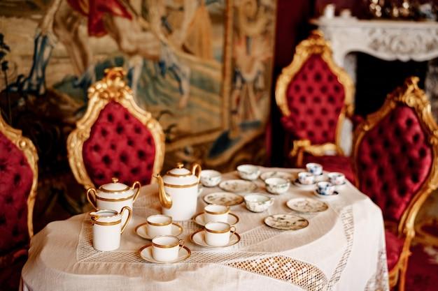 Serwis do herbaty dla czterech osób na stole z koronkowym obrusem i krzesłami ze złotą obwódką i czerwoną lamówką