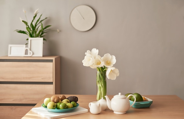 Serwis do herbaty na drewnianym stole. wystrój wnętrz domu, bukiet kwiatów w wazonie, stół z zestawem czajnika. dzień dobry koncepcja. angielskie śniadanie. śniadanie w pokoju hotelowym