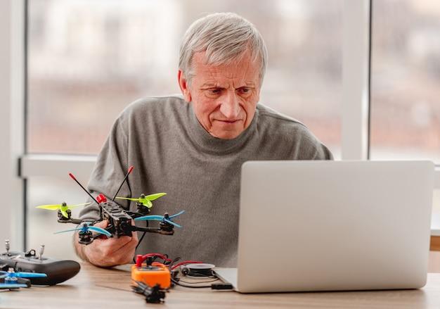 Serwis mężczyzna trzyma w dłoniach quadcopter podczas procesu naprawy i patrząc na laptopa
