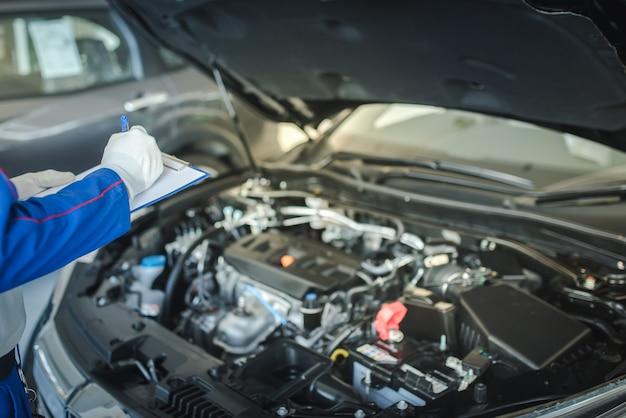 Serwis samochodowy, naprawa, koncepcja konserwacji - azjatycki mechanik samochodowy lub smith piszący do schowka w warsztacie lub magazynie, technik robi listę kontrolną dla maszyny do naprawy nowego samochodu