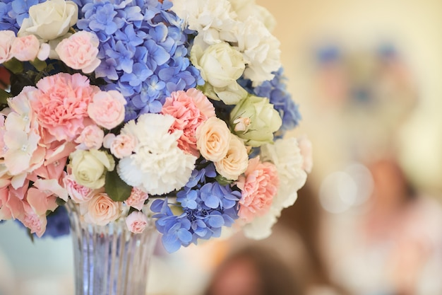 Serwis weselny. na stole stoi bukiet różowych, białych i niebieskich hortensji