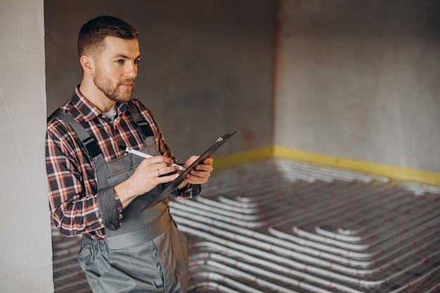 Serwisant instalujący ogrzewanie domu pod podłogą