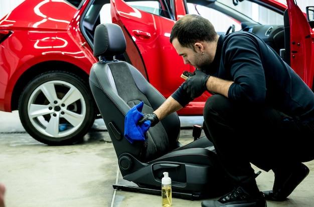 Serwisant samochodowy czyści fotelik za pomocą specjalnej szczotki