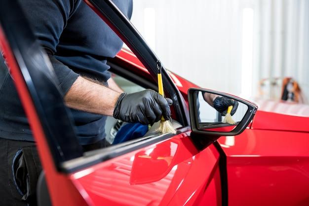 Serwisant samochodowy czyści wnętrze specjalną szczotką