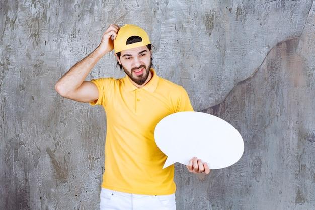 Serwisant w żółtym mundurze z owalną tablicą informacyjną i wygląda na zdezorientowanego lub zamyślonego.