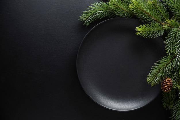 Serwowane nakrycie bożonarodzeniowego stołu w ciemnych odcieniach. ciemny talerz na ciemnym tle