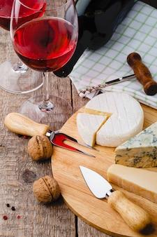 Serwowane sery i wino na starym drewnianym stole
