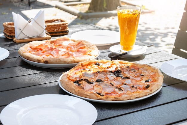Serwowanie pizzy z szynką prosciutto w ulicznej restauracji. włoskie jedzenie i herbata z rokitnika na lunch w kawiarni na świeżym powietrzu w słoneczny dzień