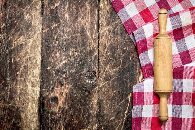 Serwowanie tła. wałek do ciasta z szmatką. na drewnianym stole.