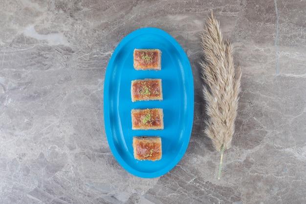 Serwowanie tureckich bakhlaw i łodyg trawy pierzastej na marmurowej powierzchni