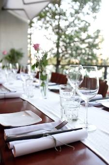 Serwowany stół ustawiony w kawiarni na tarasie o zachodzie słońca