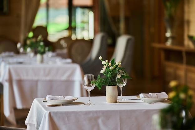 Serwowany stół z płonącymi świecami i świeżymi kwiatami na świąteczny obiad.