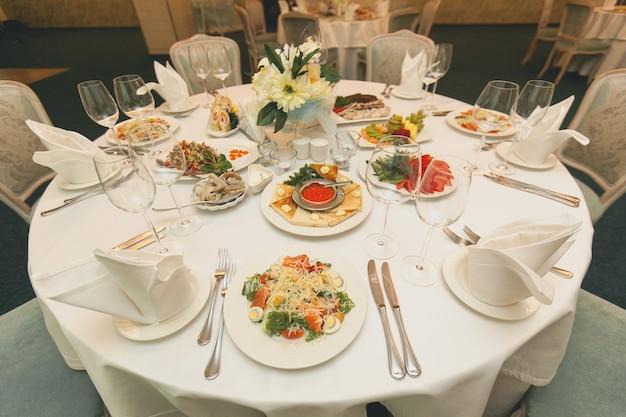 Serwujemy świąteczny stół z różnorodnymi potrawami. sałatki, ryby, owoce, warzywa, szklanki, sztućce na jasnym stole.