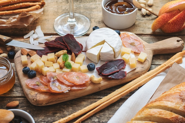 Sery i wędliny na desce z różnymi przekąskami i przekąskami, owocami i orzechami.