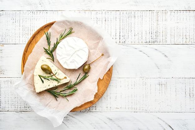 Sery zestaw lub asortyment. ser camembert, ser pleśniowy i ser brie z rozmarynem, kaparami i pieprzem.