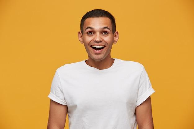 Sesja atrakcyjnego mężczyzny wygląda na szczęśliwego, radośnie, szeroko się uśmiecha, jak usłyszała dobrą wiadomość