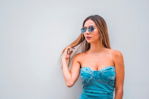 Sesja lifestyle, młoda kaukaska brunetka w niebieskiej dżinsowej sukni i okularach przeciwsłonecznych na prostym szarym tle, z miejscem na kopiowanie i wklejanie, patrząc w lewo