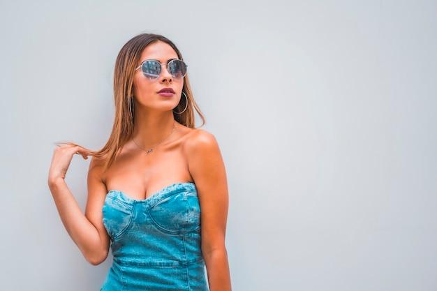 Sesja lifestyle, młoda kaukaska brunetka w niebieskiej dżinsowej sukni i okularach przeciwsłonecznych na prostym szarym tle, z miejscem na kopiowanie i wklejanie, patrząc w prawo dotykając jej włosów