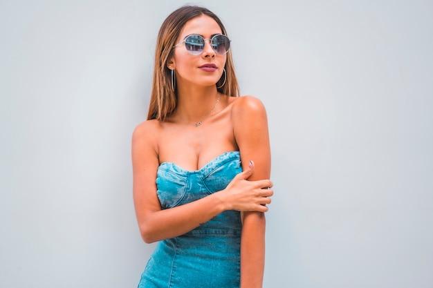 Sesja lifestyle, młoda kaukaska brunetka w niebieskiej dżinsowej sukni i okularach przeciwsłonecznych na prostym szarym tle, z miejscem na kopiowanie i wklejanie, szczęśliwy wygląd
