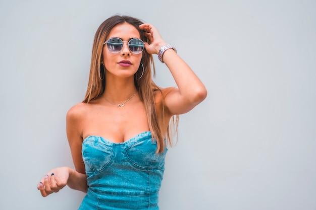 Sesja lifestyle, młoda kaukaska brunetka w niebieskiej dżinsowej sukni i okularach przeciwsłonecznych na prostym szarym tle, z miejscem na kopiowanie i wklejanie