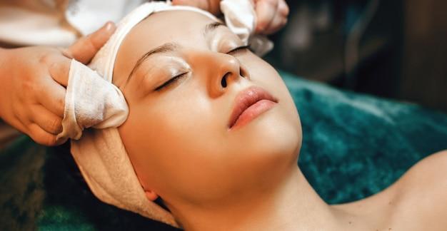 Sesja masażu głowy z młodą kobietą leżącą na kanapie spa z ręcznikiem na głowie