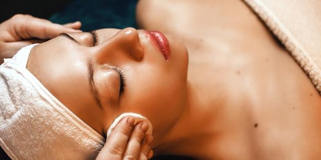 Sesja masażu twarzy z młodą kobietą leżącą w profesjonalnym salonie spa