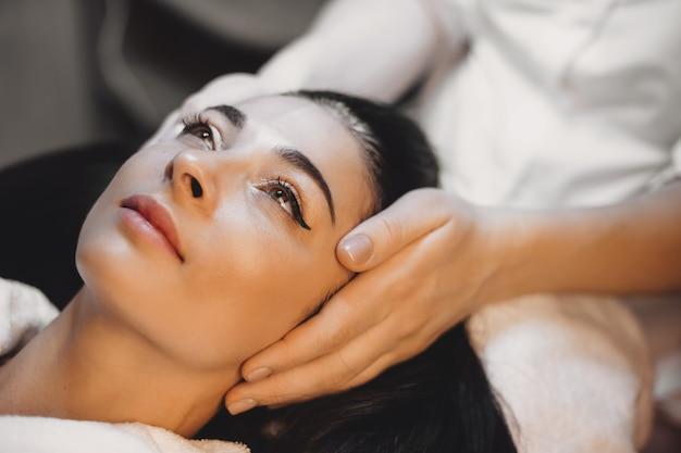 Sesja masażu twarzy z piękną kobietą o czarnych włosach w salonie spa