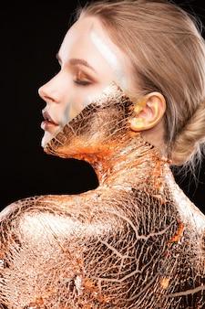Sesja piękna czarującej blondynki z kreatywnym makijażem i złotą folią na ramionach, twarzy i plecach