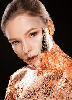 Sesja piękności modnej blond kobiety z kreatywnym makijażem i złotą folią