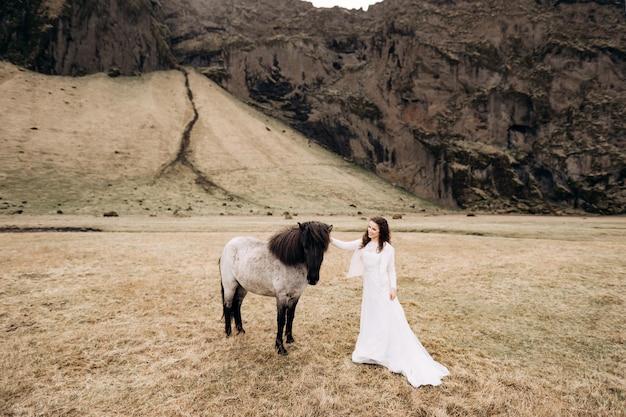 Sesja ślubna destination island z islandzkimi końmi dziewczyna w białej sukni obok