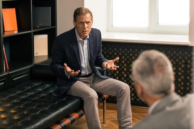Sesja terapeutyczna. przygnębiony mężczyzna rasy kaukaskiej dzielący się swoimi emocjami ze swoim psychoanalitykiem, siedząc w swoim gabinecie