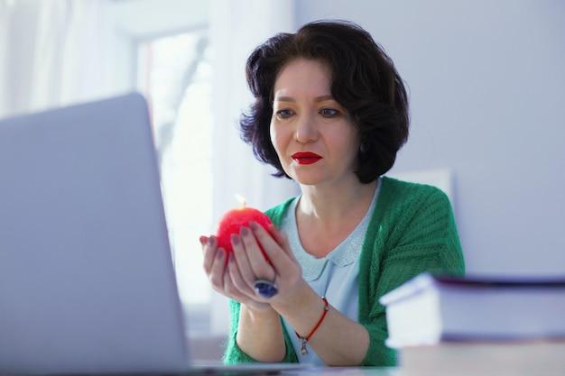Sesja wideo. przyjemna brunetka trzymająca się przed sobą za rączkę podczas rozmowy wideo
